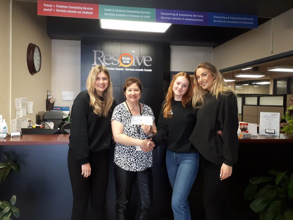 """Lauren Balogh, Mary-Claire Verbeke and April Christiansen of QLIFT present a cheque for $174.87 to Anne Gauthier of Resolve Counselling Services Canada"""